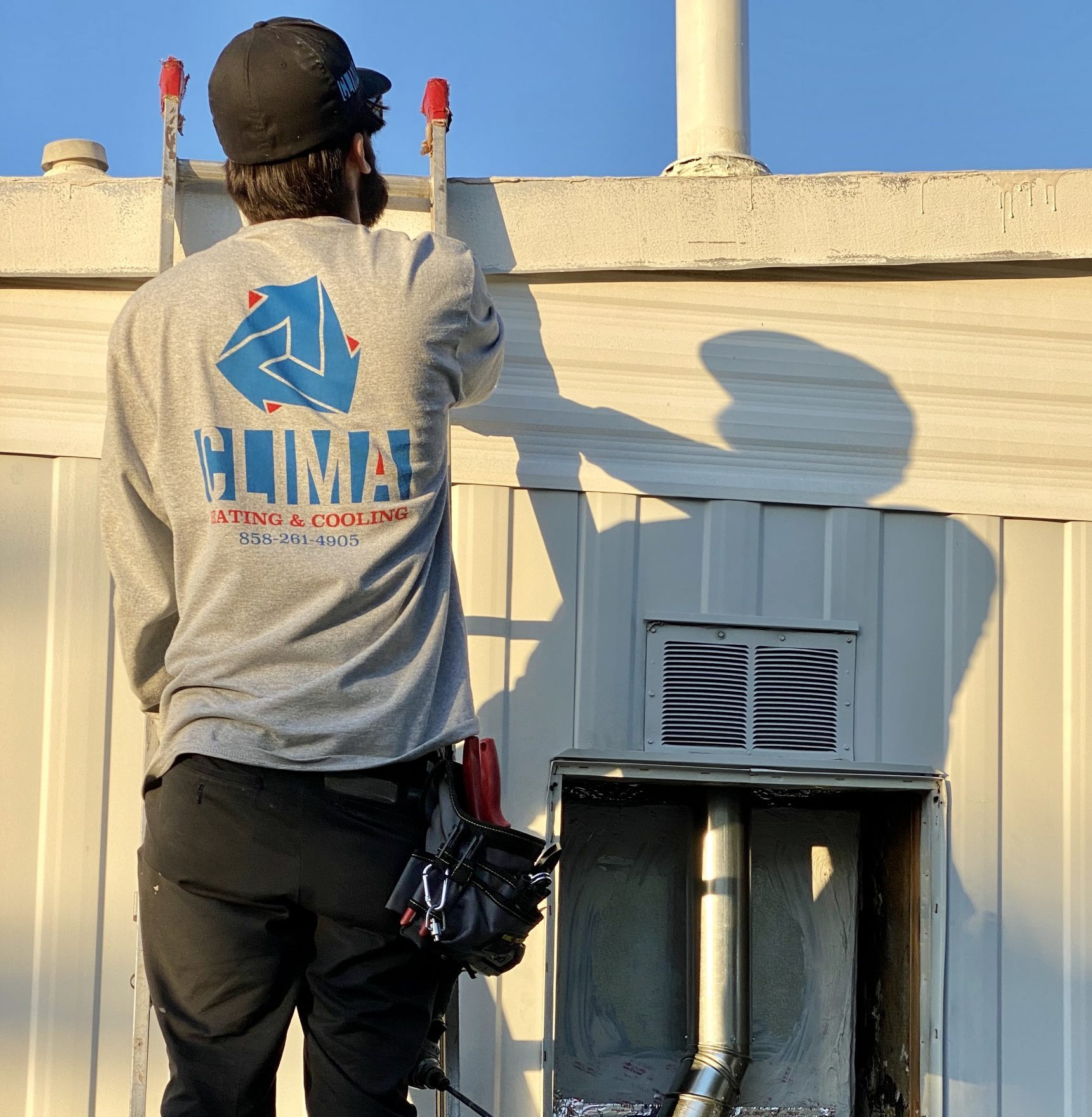 Clima Heating and Cooling technician on a ladder