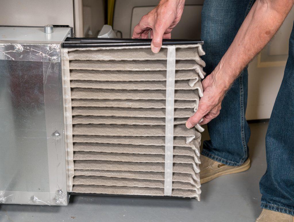 Man replacing an air filter in a furnace