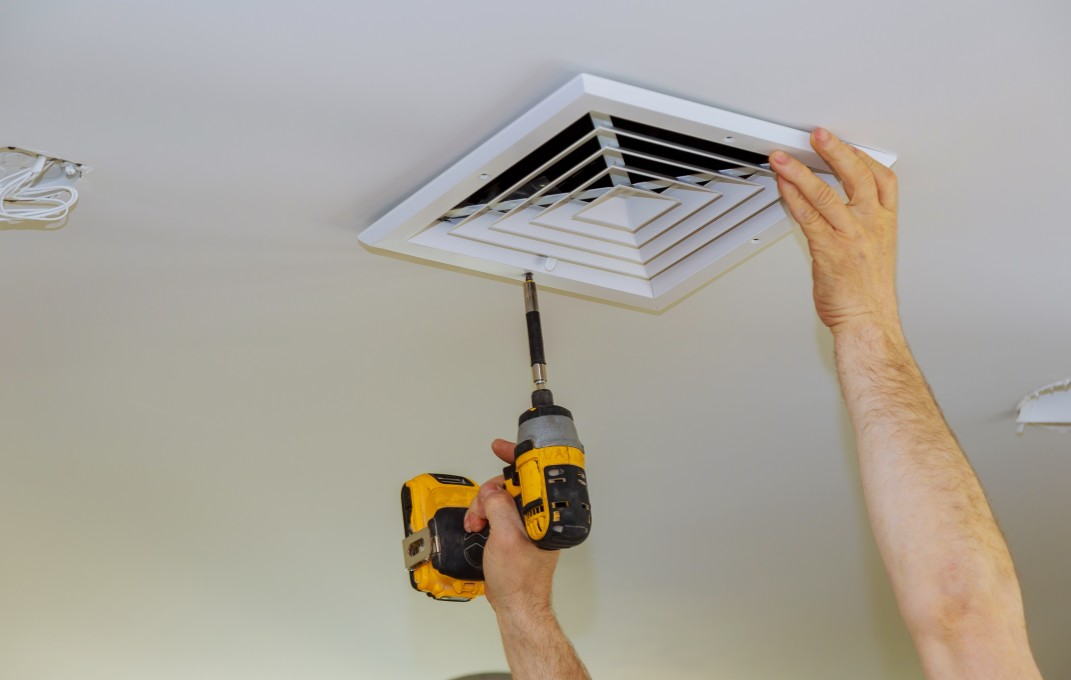 Man installing a ceiling-mounted vent